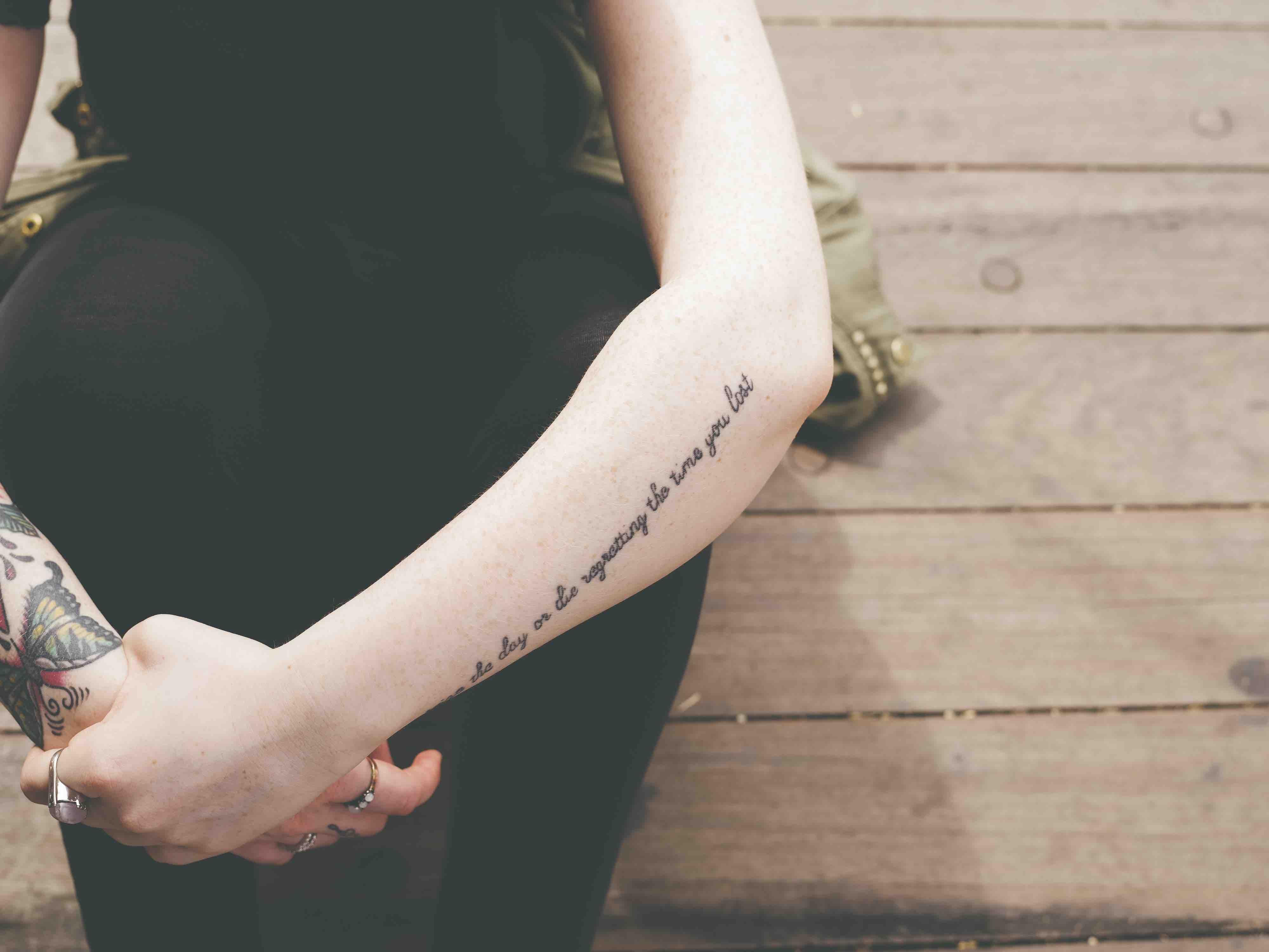 """Jeune femme assise, bras autour des jambes, avec le tatouage """"regretting the time you lost"""""""